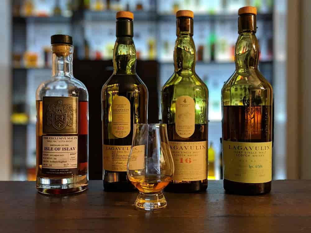 Four bottles of whisky in front of one glass of whisky
