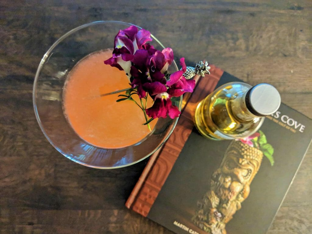 Overhead shot, cocktail glass filled with pink liquid garnished with flowers next to book with small bottle of whisky on top.