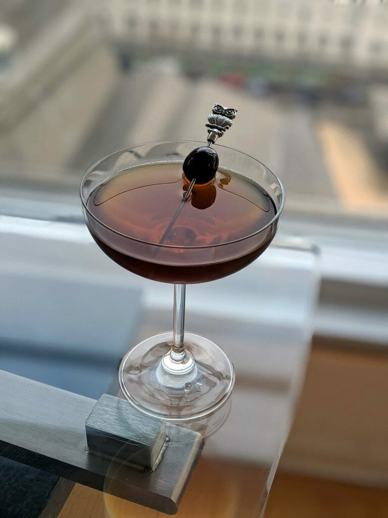Red Eye Cocktail with toothpick ontop of glass surface