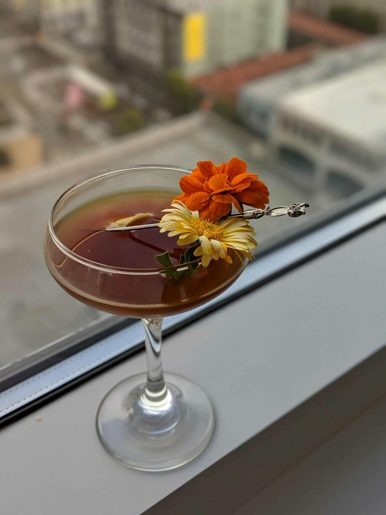 Cocktail with brown whisky and flower garnish with silver toothpick