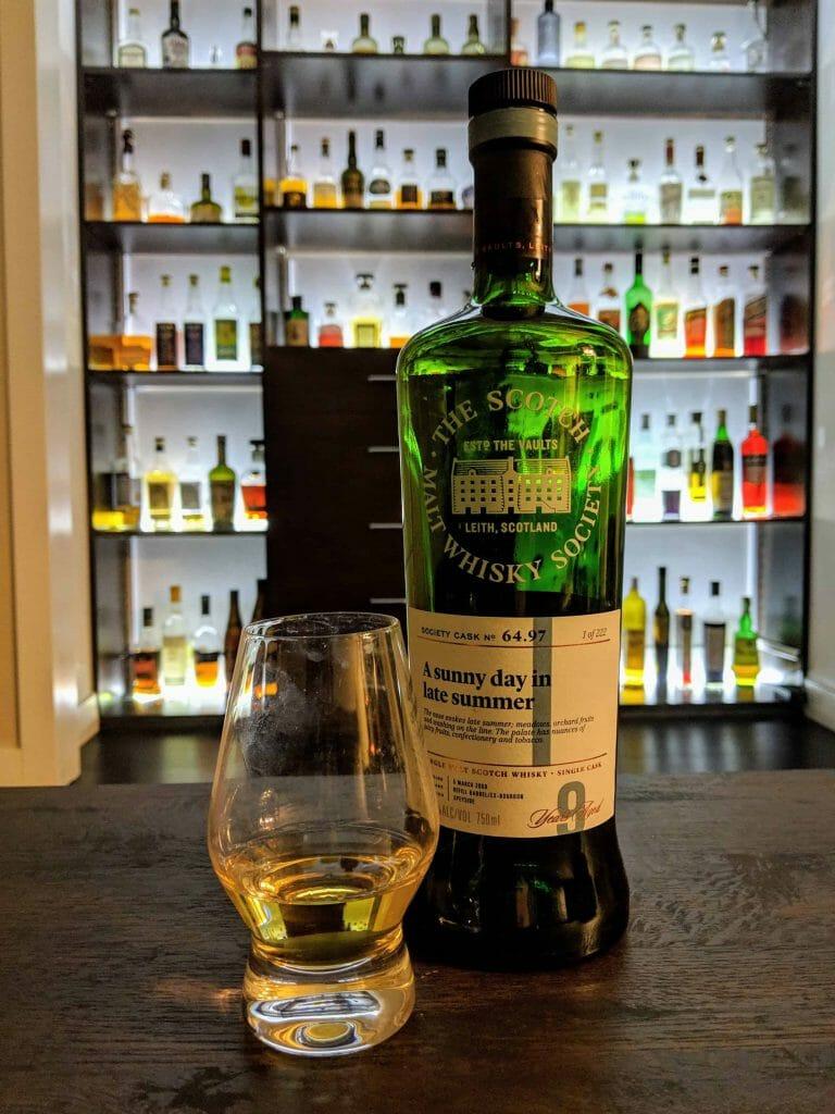 Whisky bottle next to half full glass of whisky in front of backlit bar
